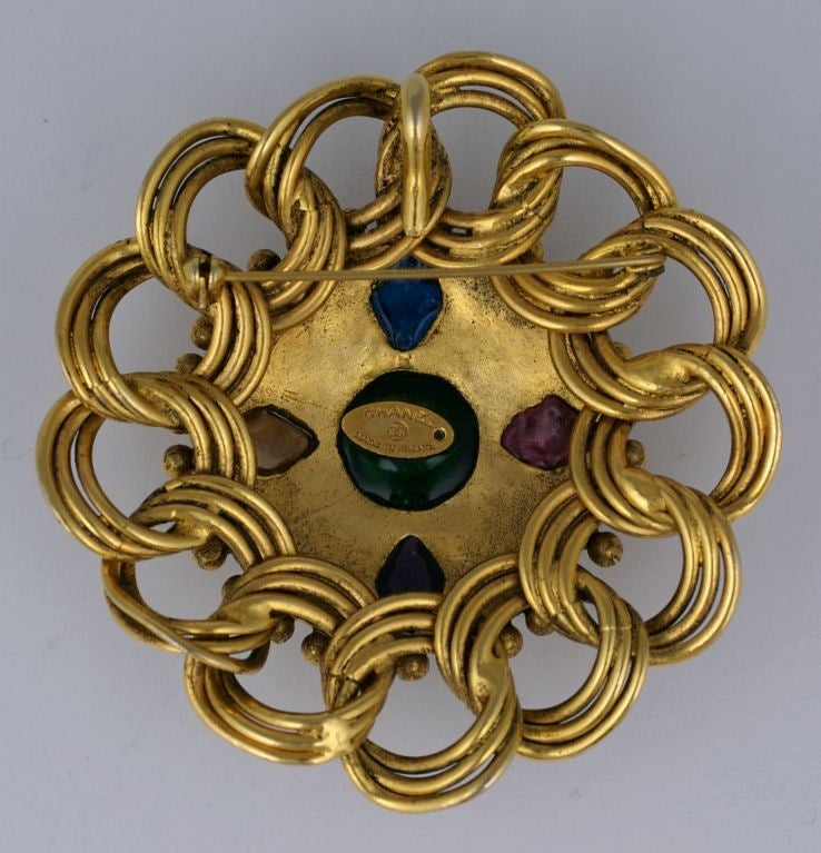 Iconic Chanel crest brooch with poured glass by Gripoix in sapphire, ruby, amythest,citrine and emerald. 4 faux  pearls in the center motif. Hand applie gilt bead and chainwork frame.