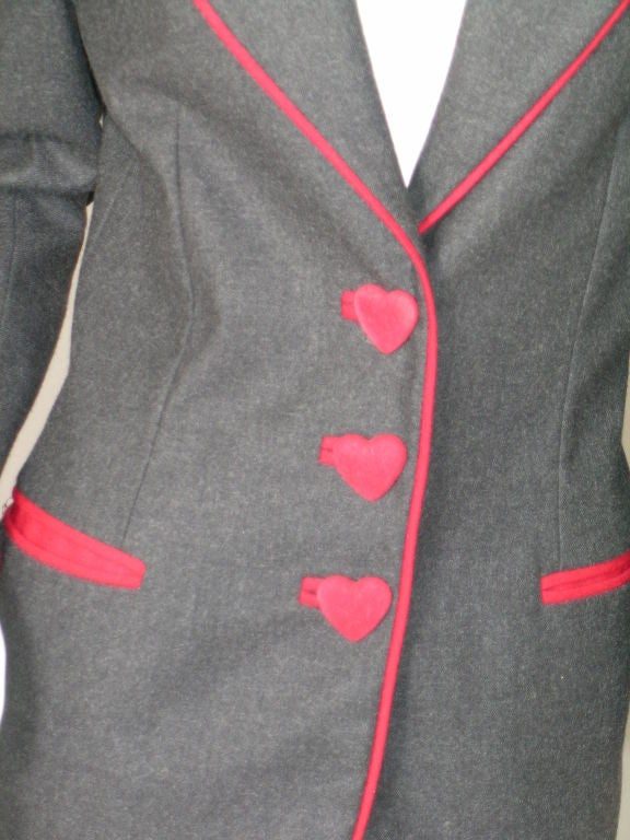 A classic charcoal grey flannel, school boy style blazer from Moschino is distinguished by the witty use of red velvet hearts for buttons!<br /> <br /> The soft grey flannel is bordered with deep red wool, which is also used to outline the bound