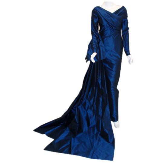 This is a long royal blue silk taffeta gown by Christian Dior Haute Couture, from 1988-89.  The gown has long sleeves, a wrapped front and back bodice, a large bow on the side hip, and two long trains.