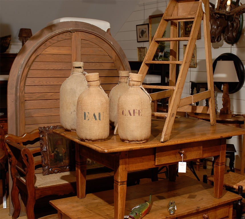 Burlap covered bottles with rope base, priced individually. French stenciling not original