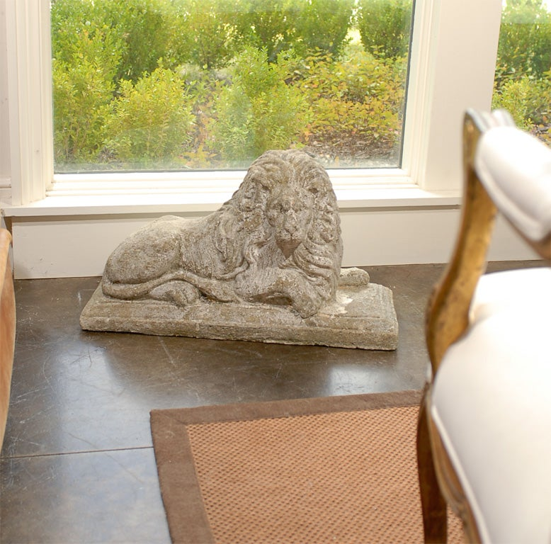A pair of English reclining stone lions circa 1920 resting on elongated bases.  This pair of reclining male lions, with their substantial manes, are relaxed but alert, with one front paw laying flat while the other seems poised to move if necessary.