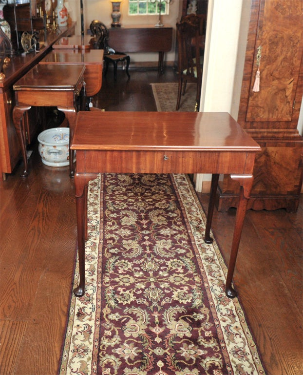 English, George III mahogany dressing table on club legs with lappet carved knee and terminating in pad feet. The interior of this table is fully outfitted with an adjustable mirror and a multitude of small compartments -- some hidden, some not --