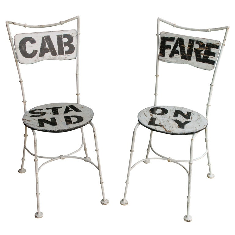 white wrought iron cab stand and fare only chairs at