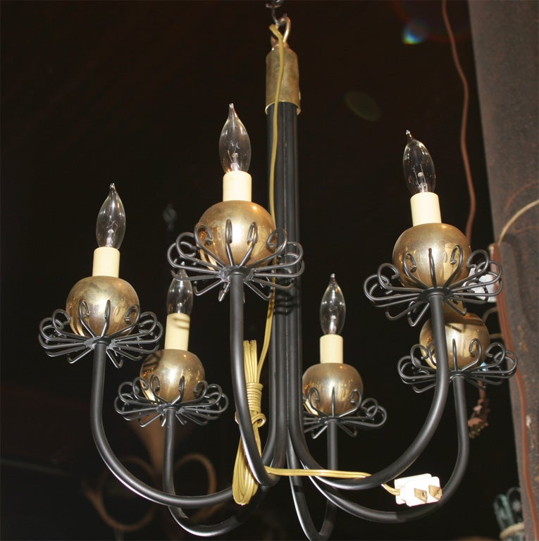 Small six-arm black metal and brass chandelier featuring brass ball and curlicue bobeches. Priced as one. Two are available.