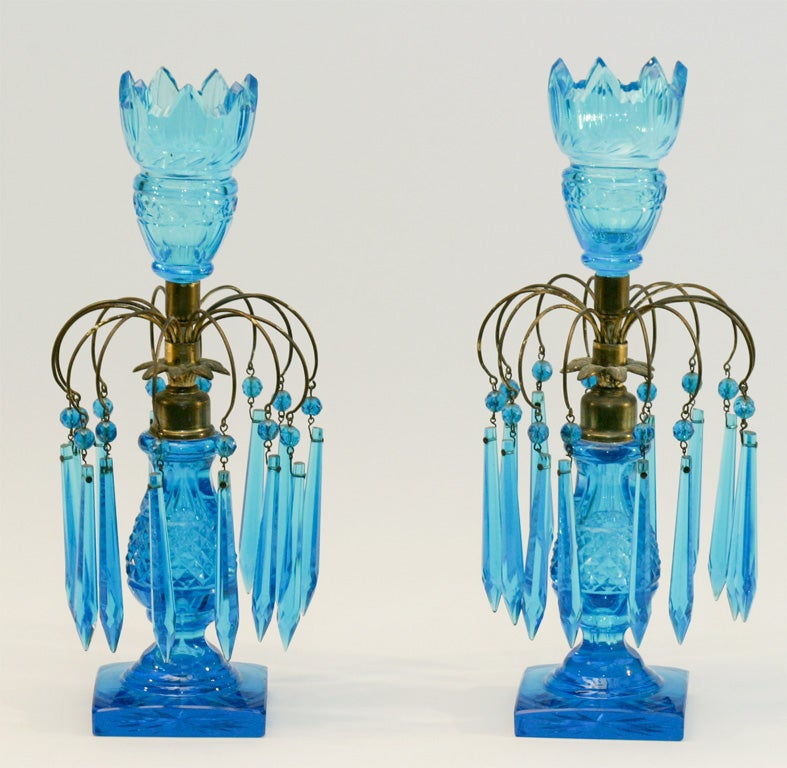 This is a superb and rare pair of period turquoise girondoles in excellent condition. Handblown crystal is cut with diamond points and star cut square base. Each one has brass mounts to hold the cut crystal prisms. Perfect for a dramatic table