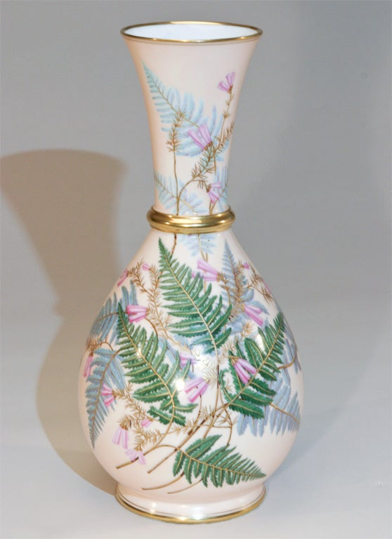 This is a finely painted decorative very large vase. The interior is white and the body, a subtle pink exterior with enamel painted ferns. It is further embellished with gold at the base, top and middle. This is both usable and makes a beautiful