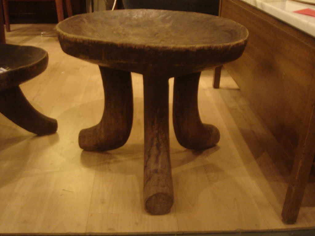 An African tripod stool. Three curved legs with concave top. Hand-carved in Africa of native hardwood, circa 1970.   Available in additional sizes in ebonized or natural dark wood finish.