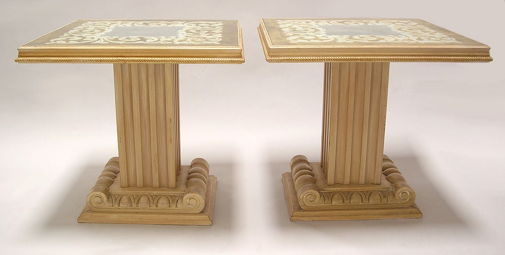 Neoclassic pair of tables made in New York by Grosfeld House, carved wood bases with inset églomisé glass tops. The backside of the glass is gilded with antique gold and silver leaf. The result is a mirror-like, reflective finish. Price is for the