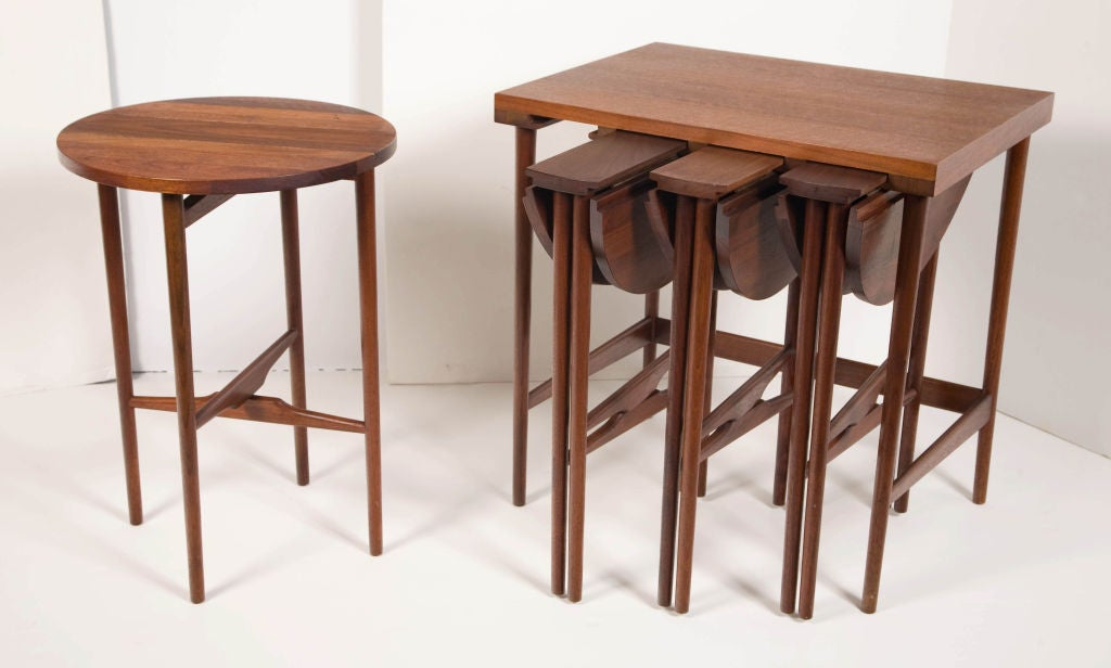 A set of four circular drop-leaf occasional tables housed in a rectangular table, all in walnut with a natural oil finish, by Bertha Schaefer for M. Singer and Sons. American, circa 1950. rectangular table: 24 1/8 x 24 x 17 1/2 in. circular tables: