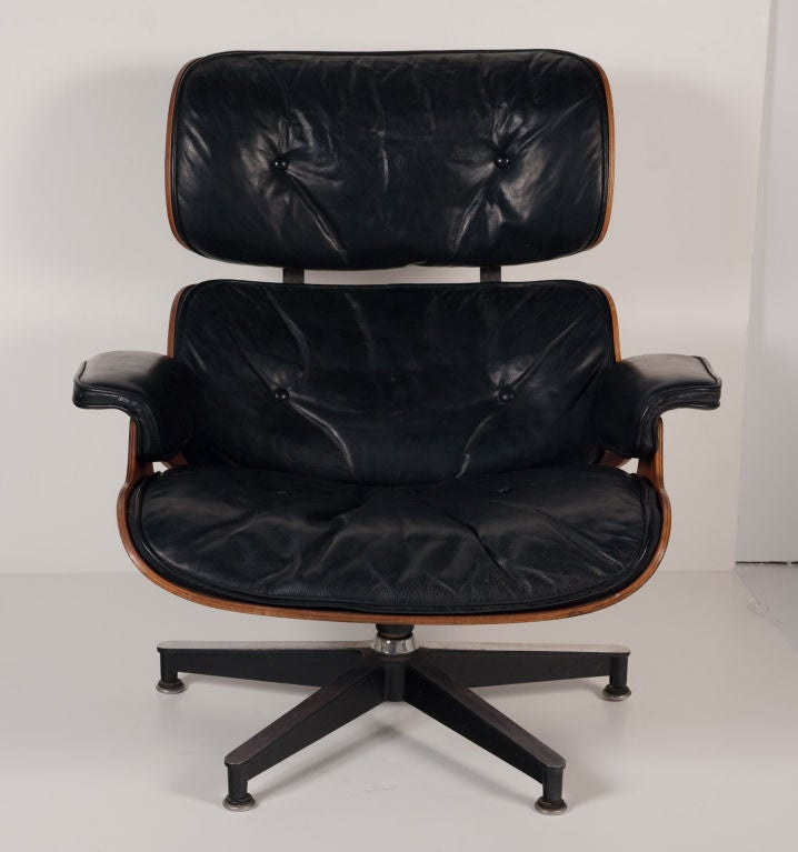 A vintage black leather and Brazilian rosewood easy lounge chair and ottoman with down stuffing. Model no. 671 and 670. By Charles Eames for Herman Miller. American circa 1950.