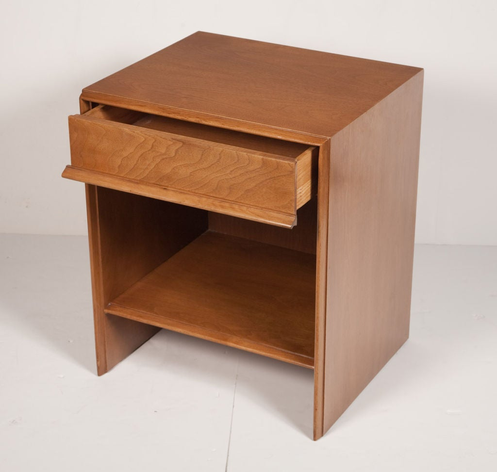 A pair of classic Mid-Century Modern nightstands in walnut, comprising a single recessed top drawer, a lower shelf and tapered round nose edge detail to the frame. With original Widdicomb label. By T.H. Robsjohn-Gibbings for Widdicomb. American,