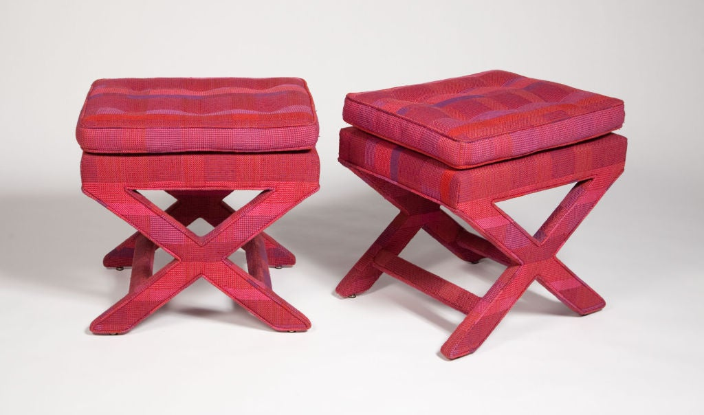 A pair of benches with fully upholstered x-frame bases. The upholstery is original Larsen fabric in a sumptuous fuchsia and violet plaid pattern. By Billy Baldwin. American, circa 1950.