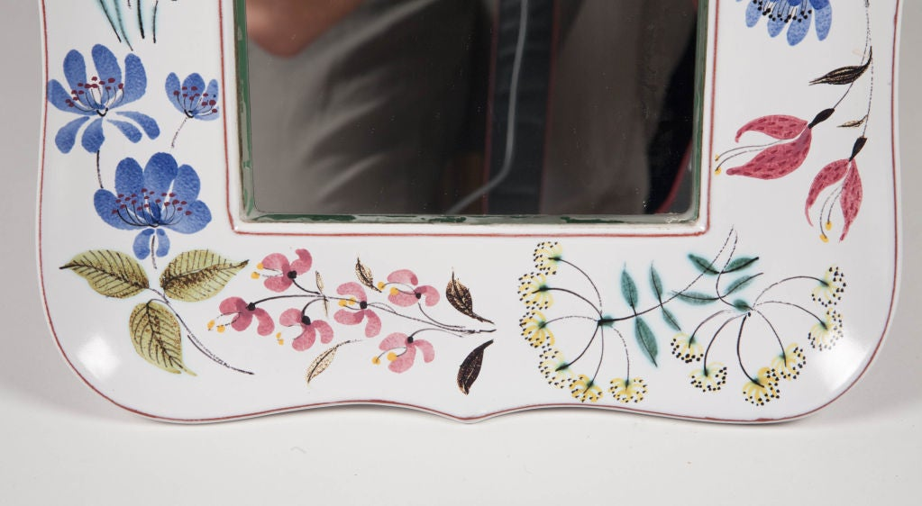 """A faience frame mirror with a hand-painted floral design to the ribbon formed frame on a white ground. Painted signature of a red star, a """"G"""" with a hand, Sweden, and """"F/10-8"""". By Stig Lindberg for Gustavsberg, Swedish, circa 1960."""