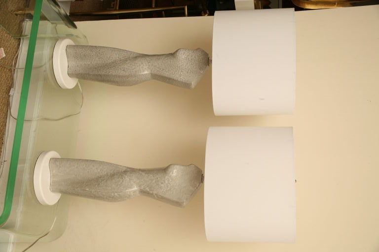 This unusual pair of sensual grey pebble glazed ceramic lamps are very sculptural. They are elegant in  torso female form and  sit on round white lacquered bases. Newly rewired. Shades used for display purposes only and are sold separately. Lamps