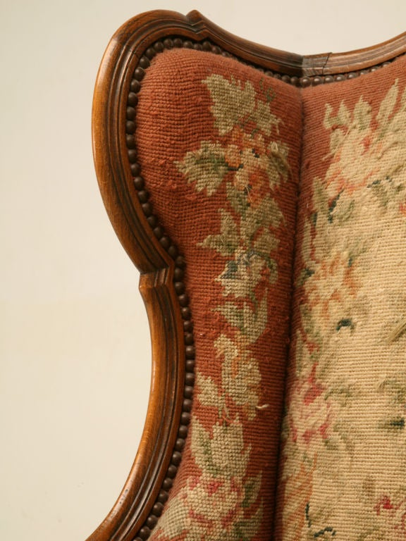 Stunning antique French Louis XV style wing-back chair with incredible needlepoint upholstery. This amazing chair would be right at home next to the fireplace in the library or study. Utilized in either a gentleman's library, or in a sophisticated