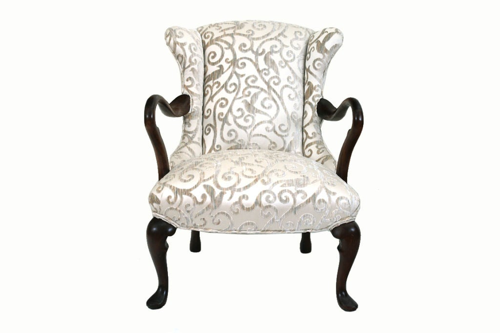 with slightly winged back, the open arms with a graceful curve, with generous seat, resting on cabriole legs and pad feet, the back legs splayed backwards