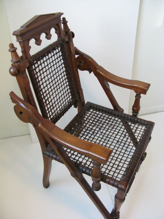 Superb Aesthetic armchair by innovative furniture designer George Hunzinger. Artfully balanced and restrained Renaissance and Moorish revival elements, given architectural bearing by patented wire mesh seat and back. The only example of this design