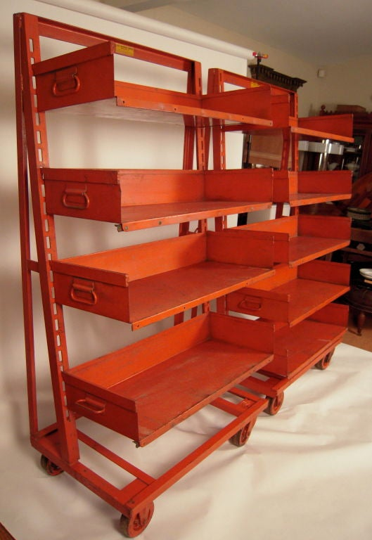 Pair of heavy duty industrial orange painted steel rolling shelving storage units, with notched sides for adjustable shelves. One unit has 4 shells; the other has 5. Easy to roll. Great color. Useful in a kitchen, library, family room or bedroom.