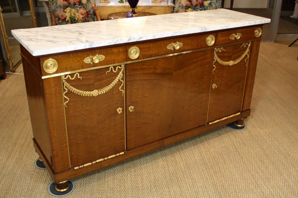 French Empire style mahogany buffet with white marble top, three drawers and three cabinets by the French manufacturer Mercier Freres. The giltbronze mounts are exquisite. Currently missing shelves, but these will be made. There is a groove cut in