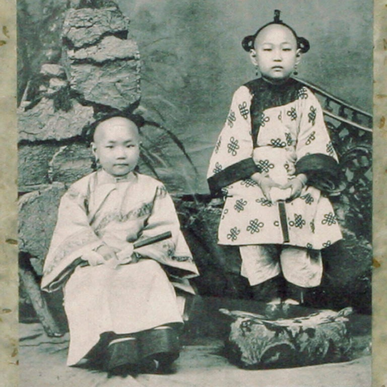 Vintage print of two young Chinese children in traditional dress, seated outside in a garden. Vintage Chinese postage stamp is affixed to upper right hand corner of image. Photo is backed with layers of textural rice papers. Wood frame has