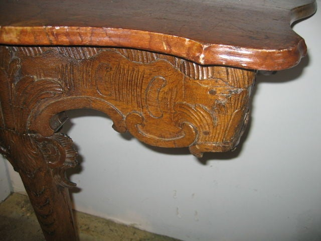 Hand carved oak console with serpentine front. Beautiful faux marble top in colors of rust and gold.