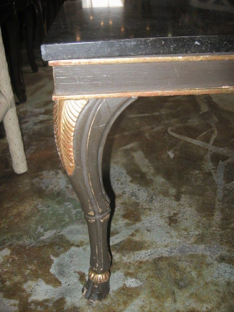 Beautifully hand carved table with dark brown-green paint finish. Gilt detailing on the goat legs and hoof feet. The knees are decorated with a carved and gilded palm frond. The marble top is a dark brown-black color.