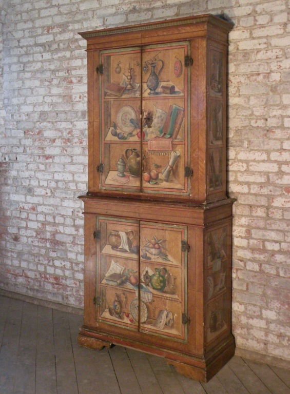 Very decorative, rare and whimsical two-part cabinet, featuring charming trompe l'oeil still lives of imaginary kitchen items. Top and bottom part with double doors. retaining original hardware, fitted with shelves.