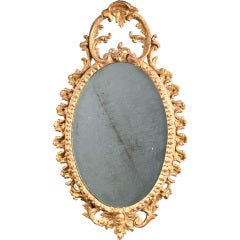 A small oval carved and Carton Pierre mirror