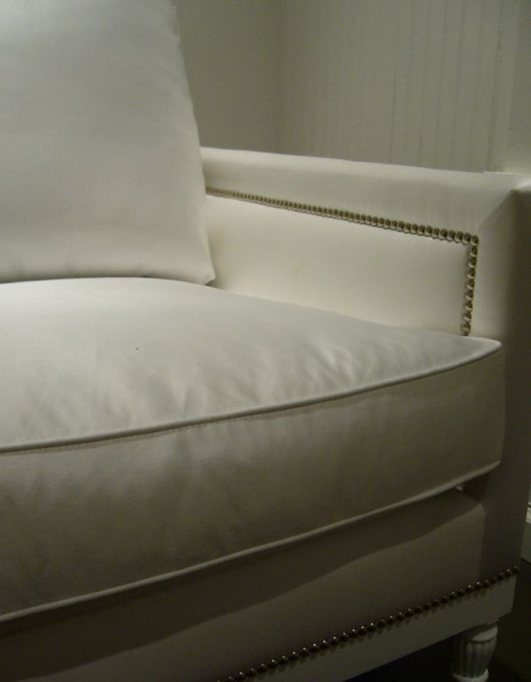 White satin sofa with nailhead detail, from a one of a kind set modeled after specific pieces from Coco Chanel's apartment in Paris.