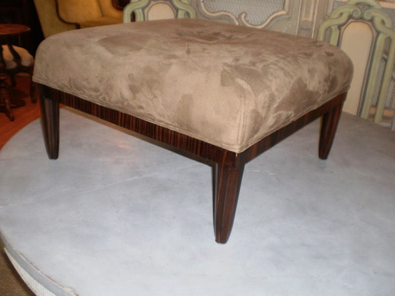 Stunning large 1930s French Art Deco upholstered ottoman, stool or bench. This square French bench is made of exotic Macassar wood, upholstered in ultrasuede fabric with a large square button in the center.