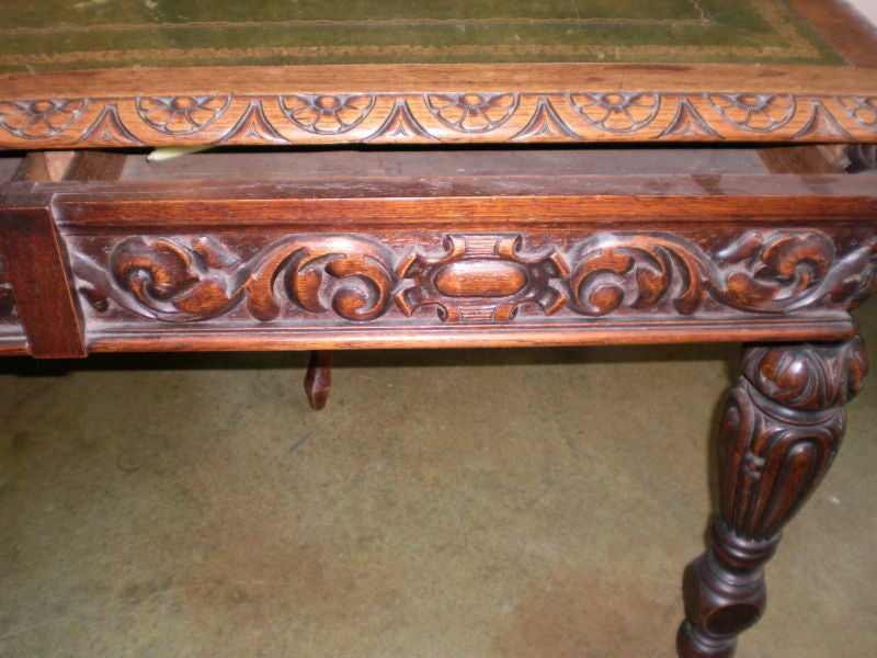Northern Italian two-drawer carved walnut desk with distressed gilt embossed green leather top. A beautiful desk or writing table with a good sized surface area. This versatile piece could be used as a side table or center table.