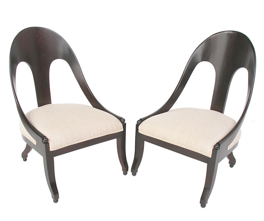 Sculptural Pair of Spoon Back Chairs, circa 1950's. These sexy low slung chairs look great from every angle! They are executed in a deep brown finish over the walnut frames, with ivory colored linen upholstery. Price quoted in this listing if for