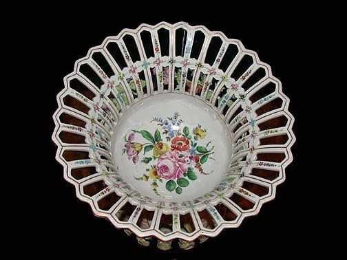 This highly decorative footed bowl, reticulated and painted with flowers, is raised on a charmingly decorative base modelled with dancing putti on a flower-strewn ground.