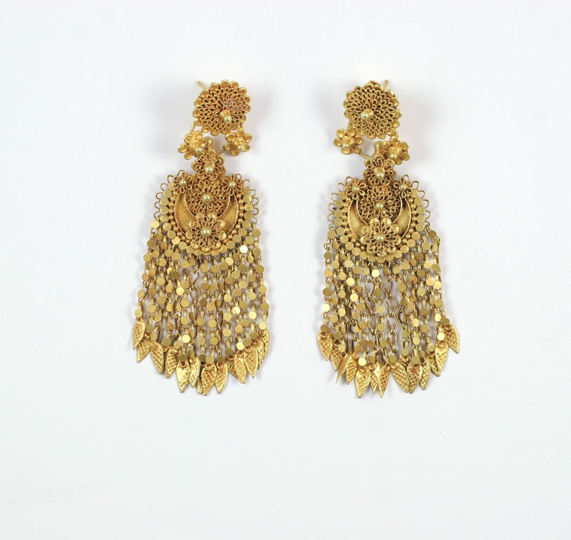 A pair of 18kt yellow gold earrings. The earrings have a flower garden at the top of each earring and cascading chains fall down from the garden with leaves dangling at the ends.