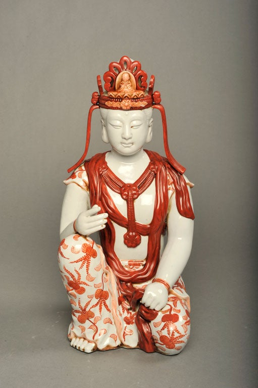 A vibrant porcelain Bodhisattva sculpture flawlessly hand-painted in coral, Japanese, circa 1960.