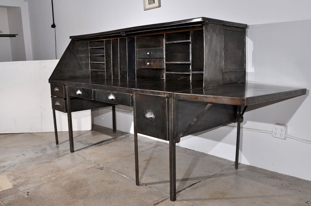 an oversized french desk in steel with a drop-leaf side and a cover that pulls down.