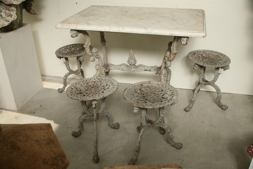 A suite of grey painted cast iron garden table with original white marble top, and four tabouret stools. Measures: Table W 35.5