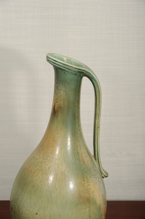 Handmade stoneware pitcher with applied handle and pale green feather glaze. Signed on underside.