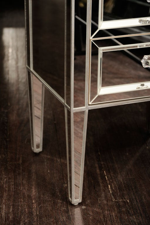 Pair of custom mirrored commodes with silver trim.