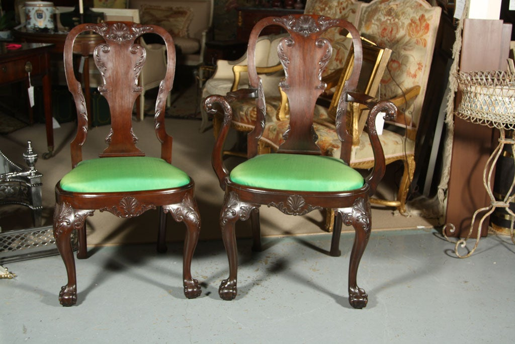 A set of eight Irish Georgian style mahogany dining chairs consisting of two arms and four sides having ballaster form splat back ending on ball and claw feet with newly upholstered drop in seats.   Armchairs measure 41.5 H x 28 W x 22.5 D.