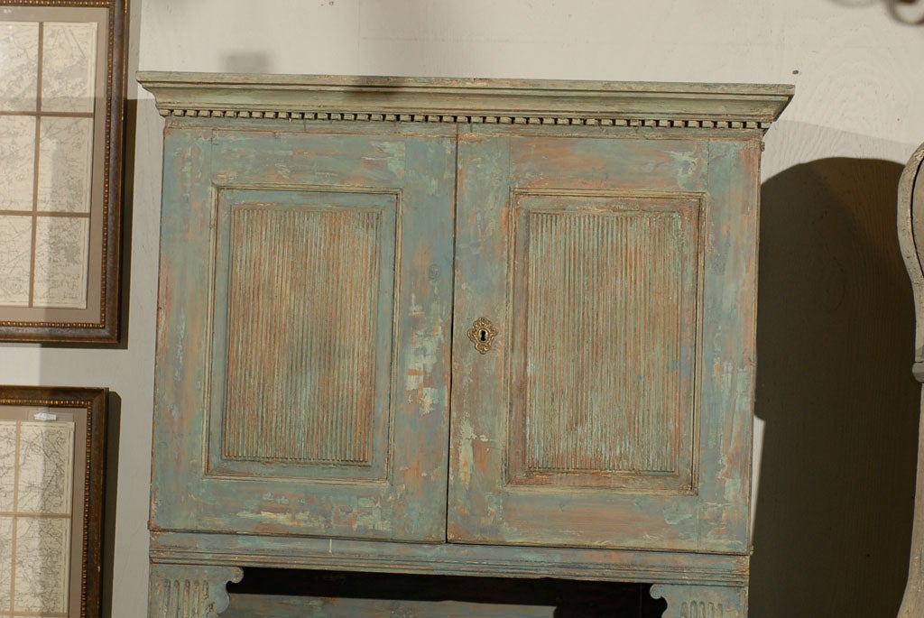 A 18th century Swedish late Gustavian cabinet with original paint. This cabinet has four doors, stationary shelves and bun feet, dentil molding and reeded doors. The feet have been replaced.