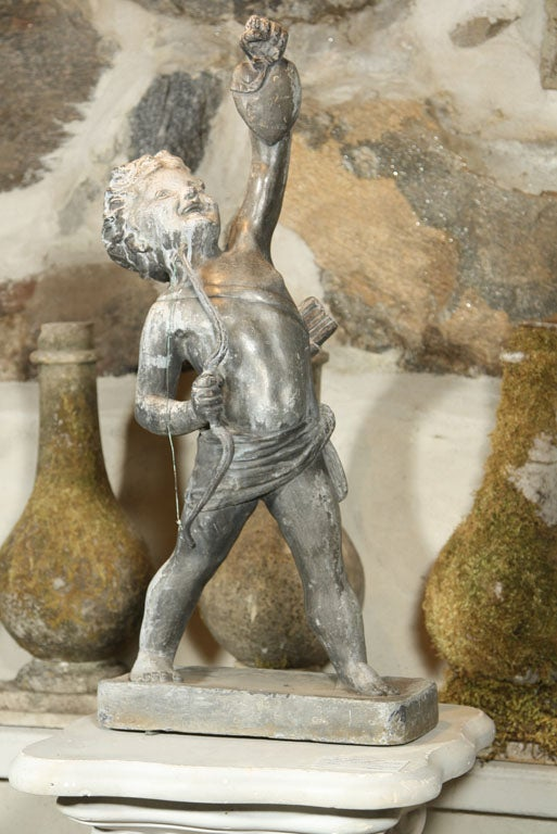 This rare lead statue of cupid, unsigned but catalogued in 1905 by the famed Arts & Crafts Artisans' group, Bromsgrove Guild, features a triumphant Cupid with quiver and copper-stringed bow, holding aloft a heart. Wonderful detailing to head,