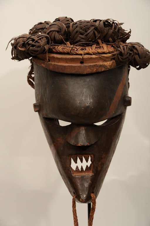 Fiercely visaged mask with bulbous forehead, filed teeth, and original woven fiber head piece. Rakish marking painted in red is an unusual and graphically arresting feature. Measurements include stand.  The Salampsasu tribe was from the Congo, and