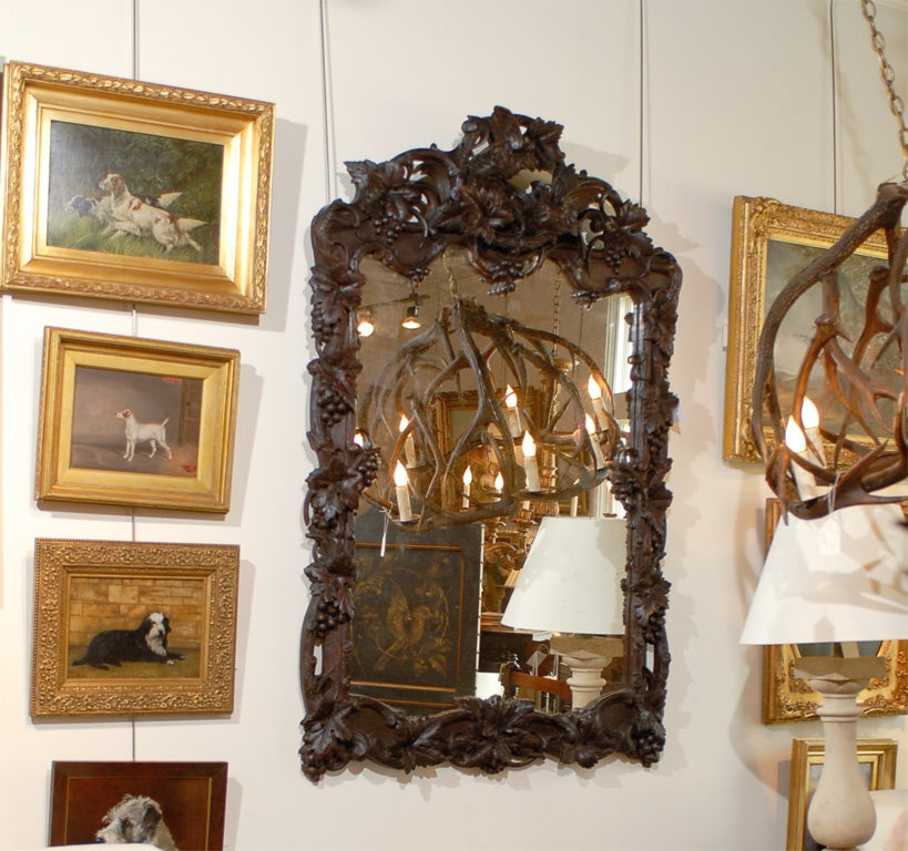 This large late 19th century French mirror is set within a rectangular carved Black Forest style crested wooden frame. The intricate decor is composed of beautifully detailed openwork intertwined vines with leaves and grapes while a bird with its