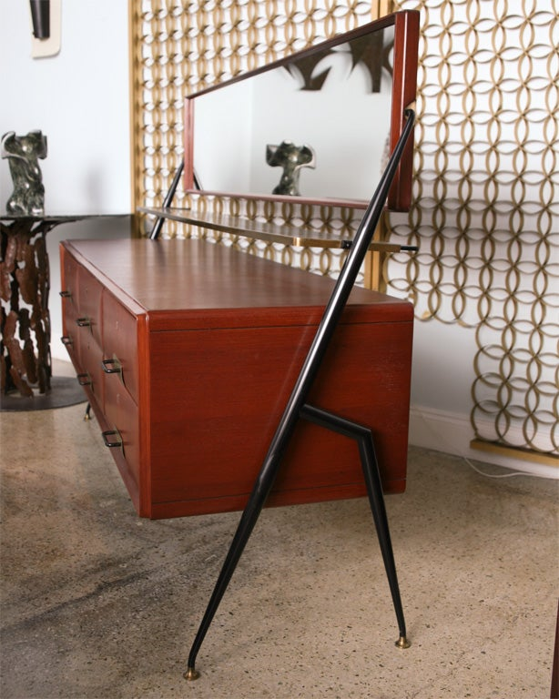 The swivel mirror above a fixed glass shelf trimmed in brass, over a mahogany case with six drawers with brass pulls, resting on an iron geometric Stand- can be sold separately- note height 1 oi overall to top of mirror- height 2 is to top of wood