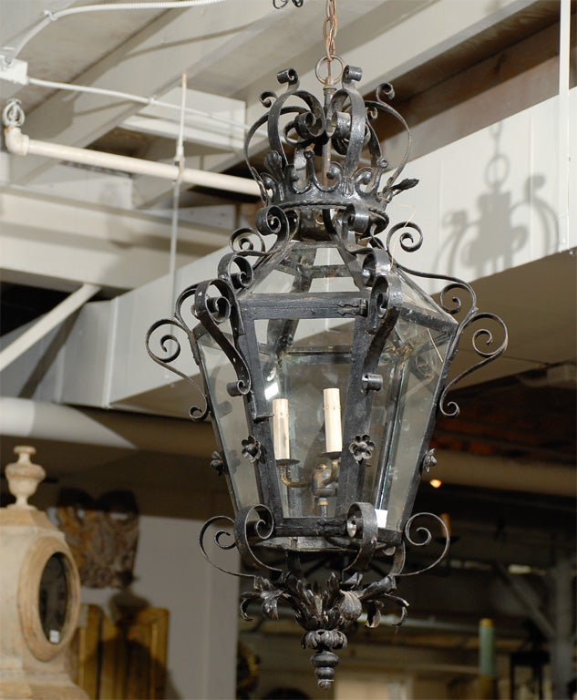 An exquisite large size French wrought iron and glass lantern with three-lights, topped with an iron crown. This French hexagonal lantern from the mid 20th century features an elegant decor of volutes, acanthus leaves in its lower section as well as