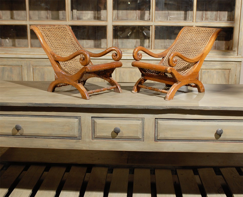 A pair of 19th century British Colonial chairs made for children with cane seats, nicely carved arms and half-moon legs.