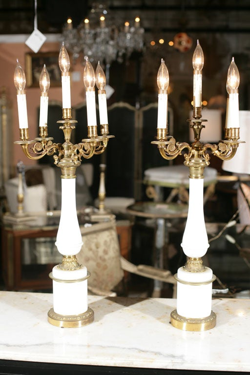 A pair of candelabra, each electrified, the five arms supported by bronze and milk glass stands.