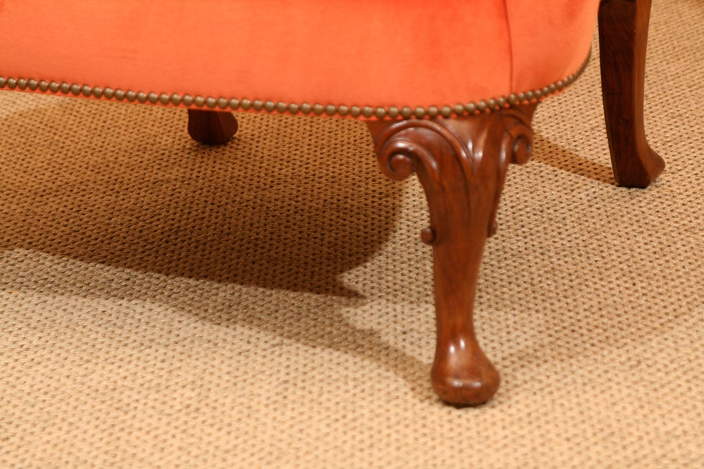 A late 19th century walnut wing armchair on moulded cabriole legs with carved knees on pad feet upholstered in orange cotton velvet and hand loomed pink and orange silk Ikat with nailhead trim.