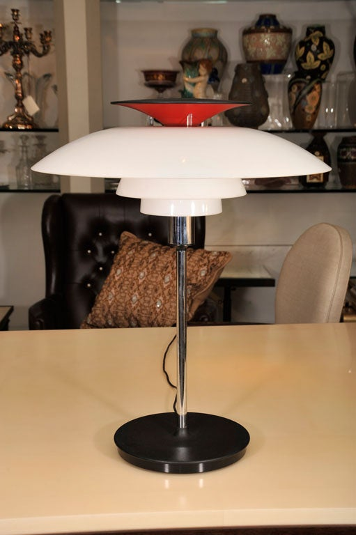Chrome table lamps with red and white plexi domed shades on round black base.